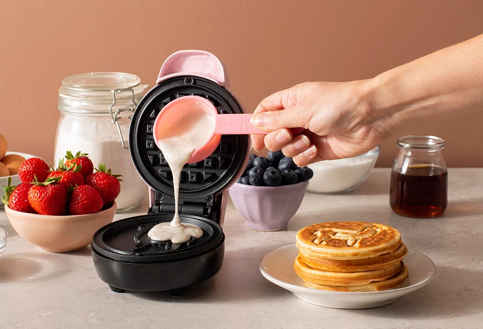 hand pouring waffle batter into a waffle maker