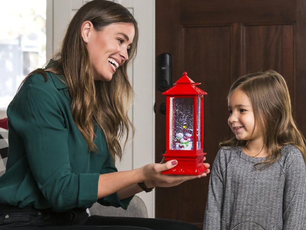 woman holding snow globe next to little girl