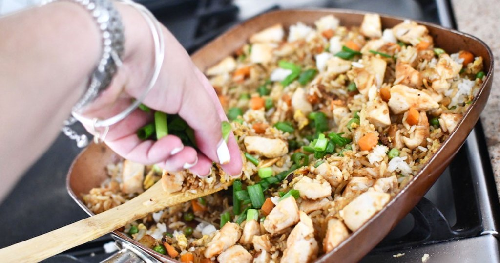 putting green onions on chicken fried rice