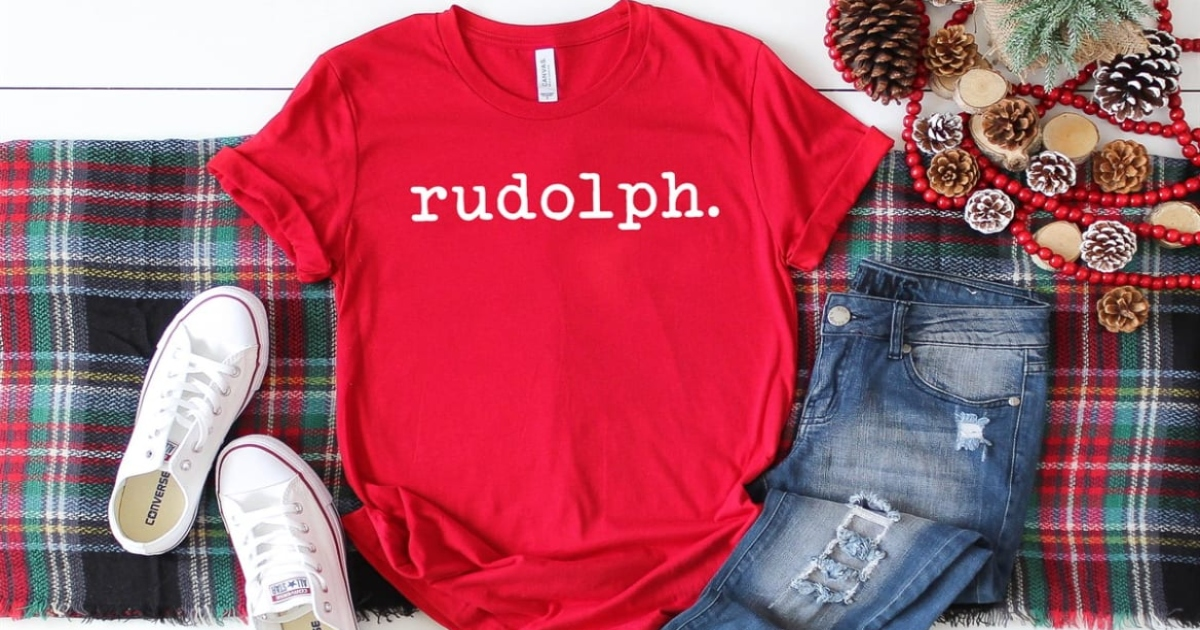 red rudolph tee laying out with a pair of jeans and white sneakers on a plaid holiday table runner