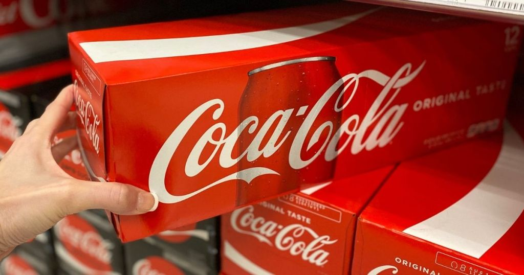 hand holding a 12-pack of coca-cola