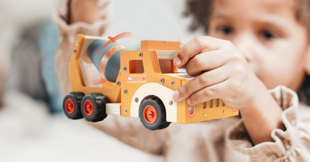 child holding a wood cement truck