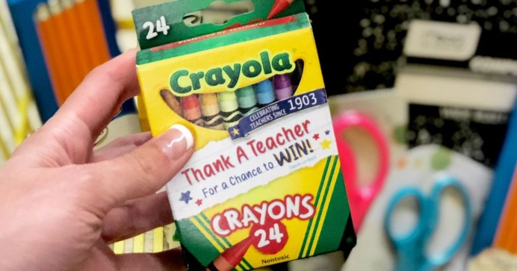 hand holding a pack of crayons