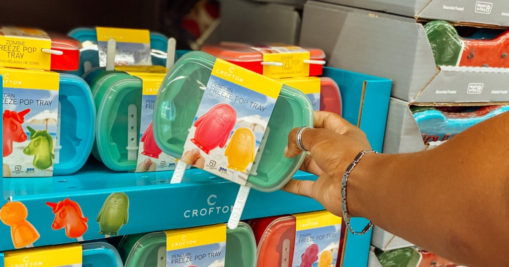 hand holding package of penguin popsicle molds near in-store display