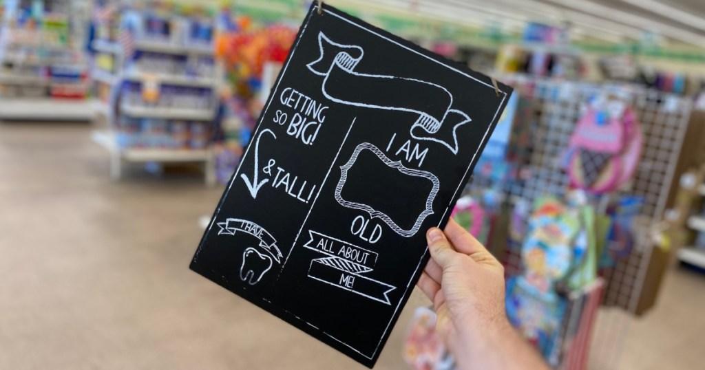 hand holding baby milestone chalk board near in-store display