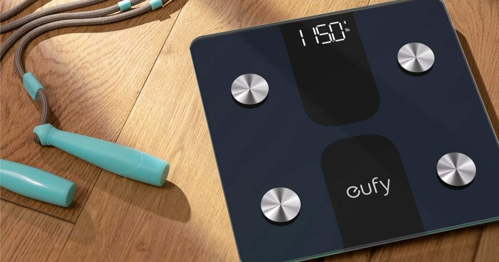 eufy brand smart scale on hardwood floor near jump rope