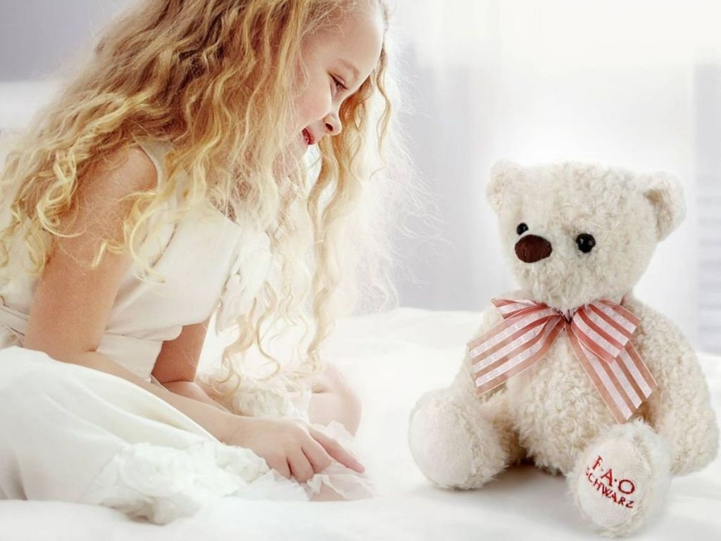 little girl sitting on bed with teddy bear