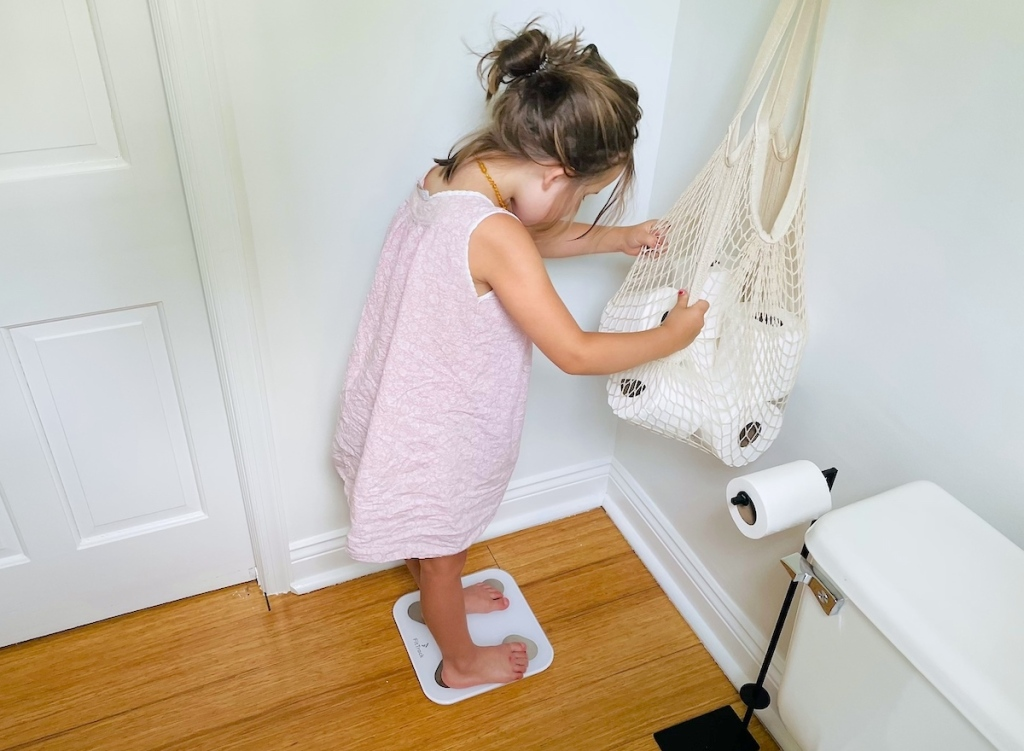 girl standing on smart scale in bathroom