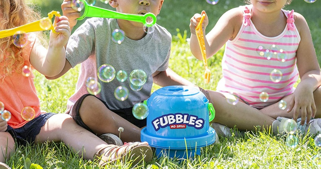 kids blowing bubbles with blue bubble bucket in front of them