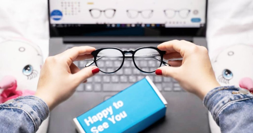 woman holding glasses in front of laptop with glassesusa pulled up on computer