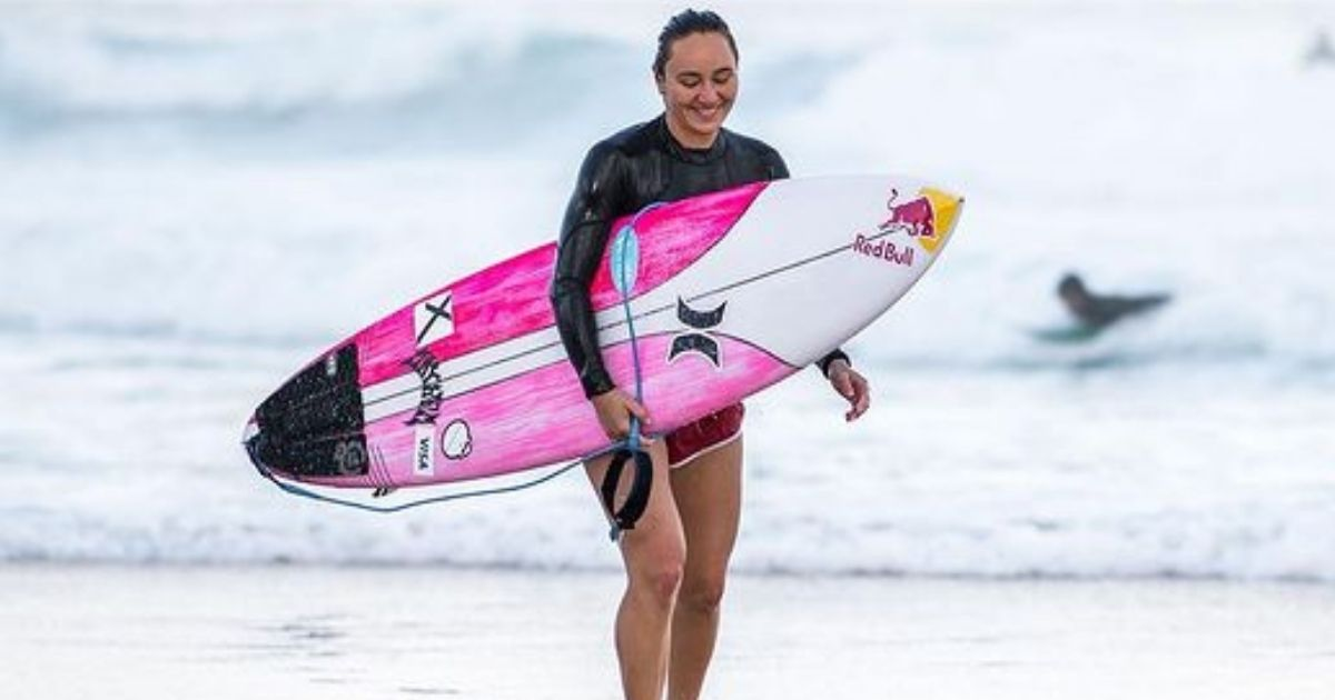 woman carrying a surfboard