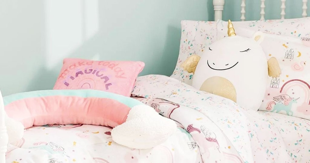 bed with throw pillow and unicorn plush