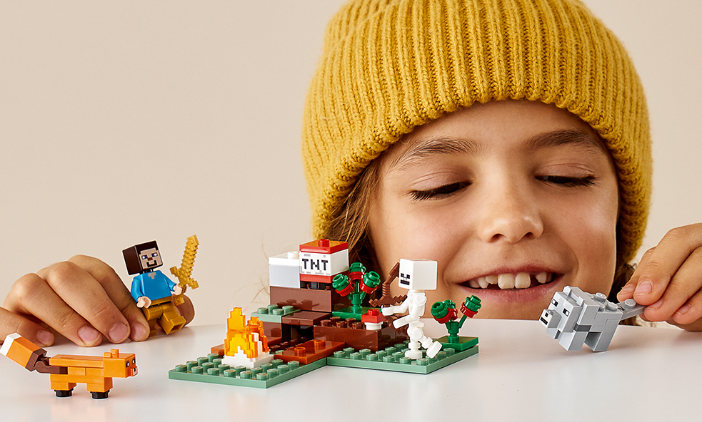 kid playing with a LEGO minecraft set