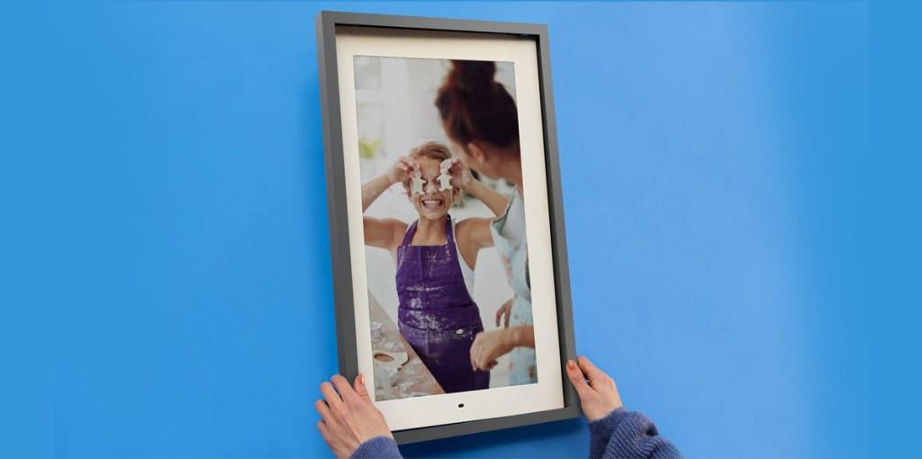 hand holding smart frame near blue wall