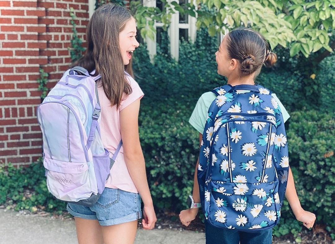 two girls wearing backpacks