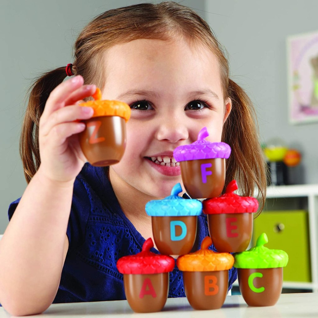 girl playing Learning Resources Alphabet Acorns Activity Set