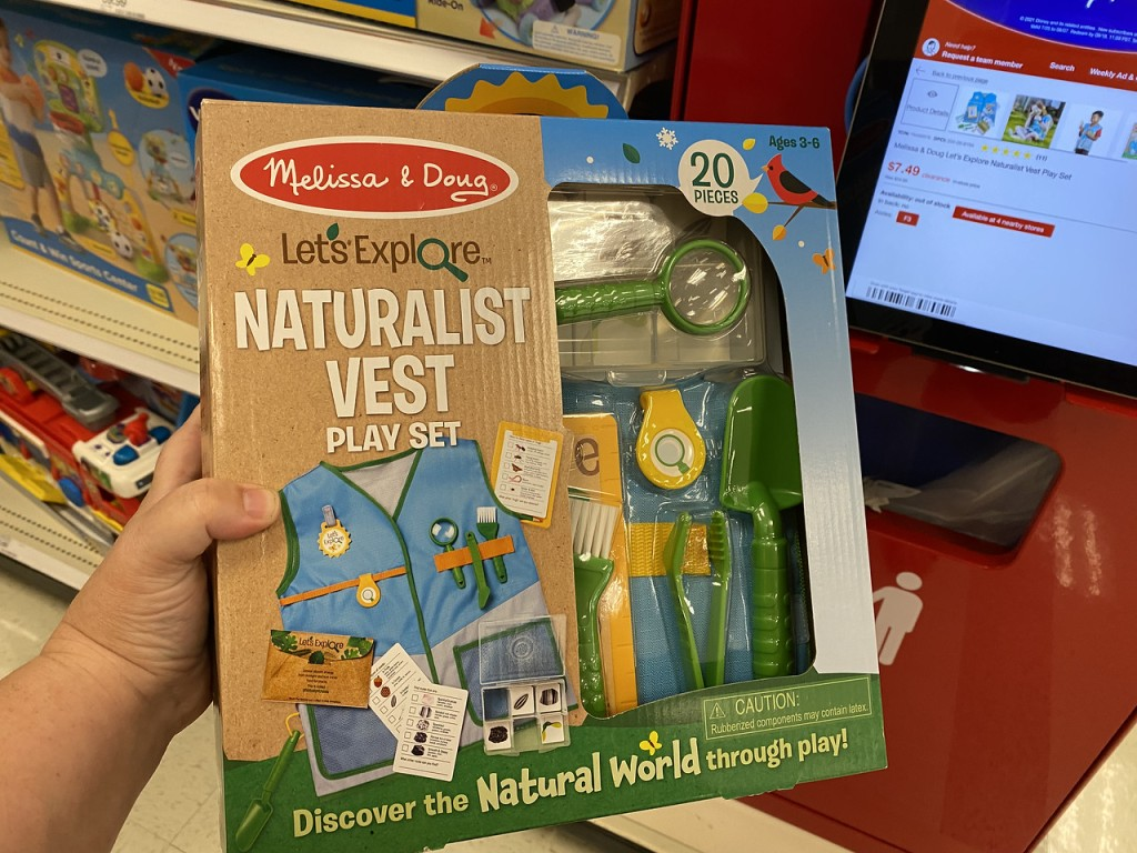 Hand holding upLet's Explore Naturalist Vest in store