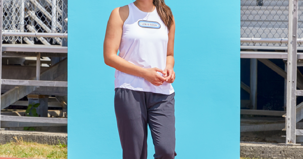 woman wearing a life is good tank top standing in front of a blue background