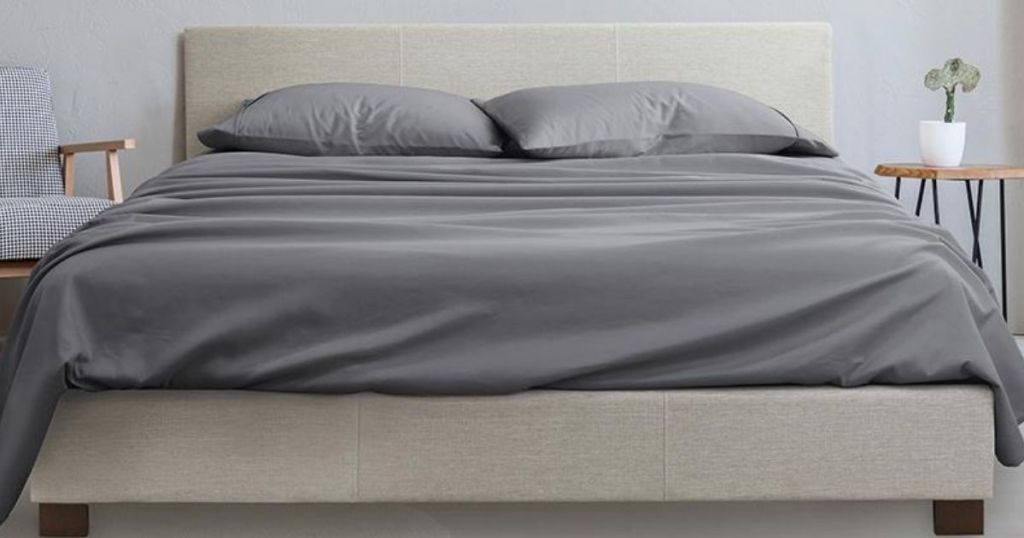bed with grey sheets on it