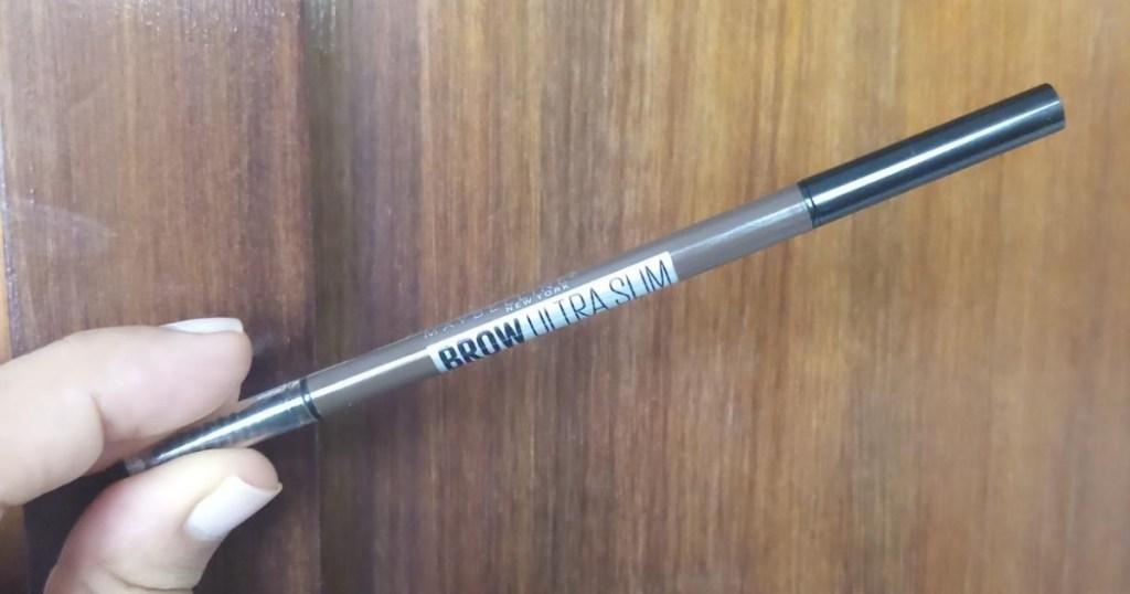 hand holding Maybelline brand brow brush