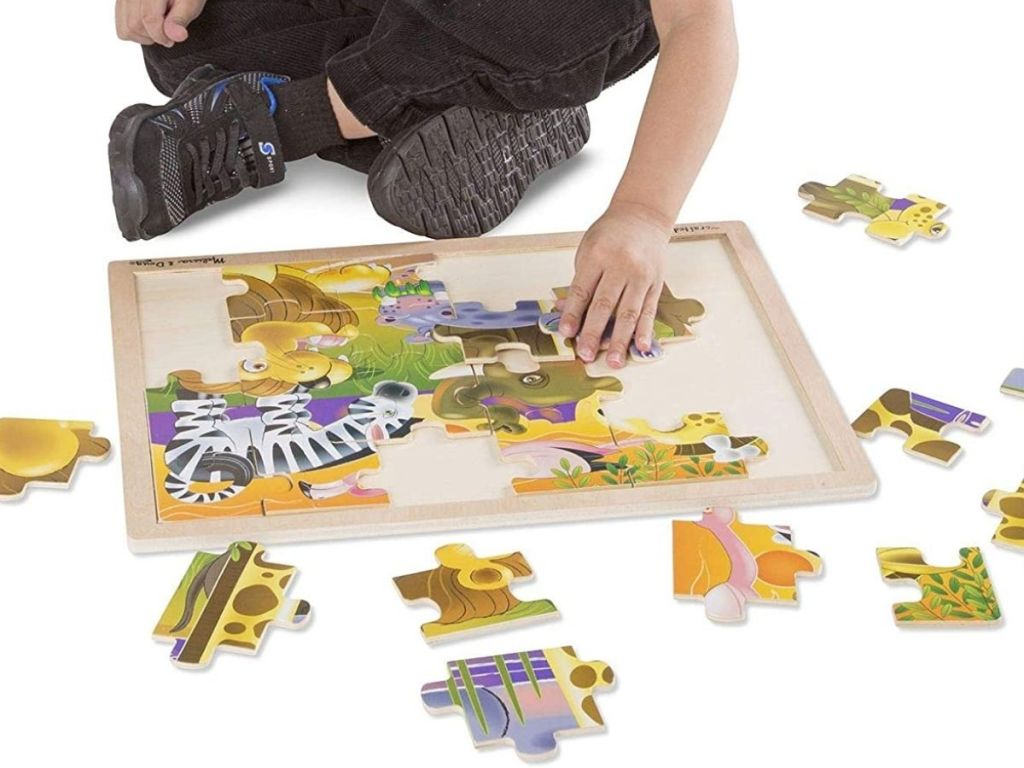 boy putting jigsaw puzzle together