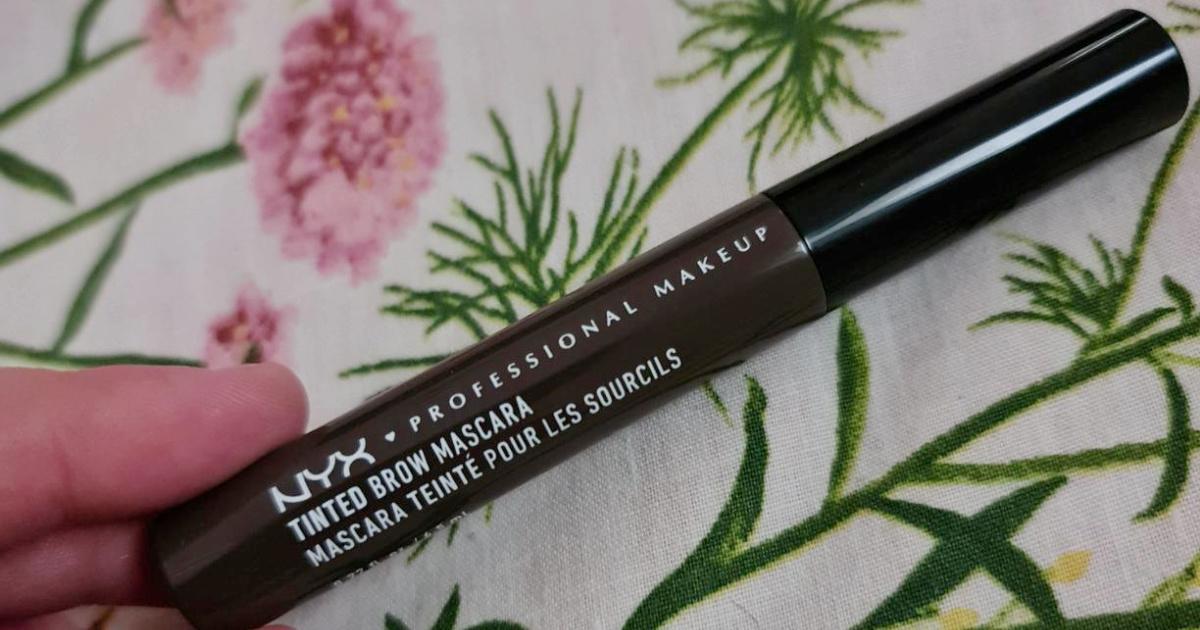 hand holding a tube of NYX Professional Makeup Tinted Brow Mascara