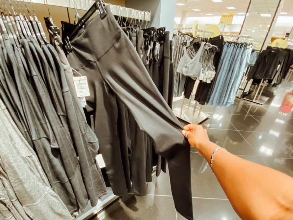 woman pulling out leggings from rack