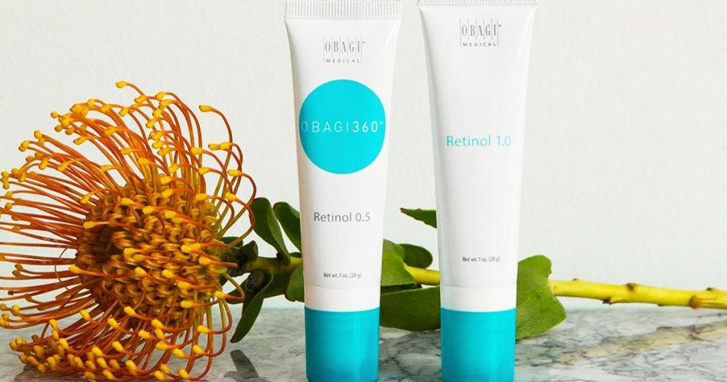 two tubes of obagi retinol cream near flower