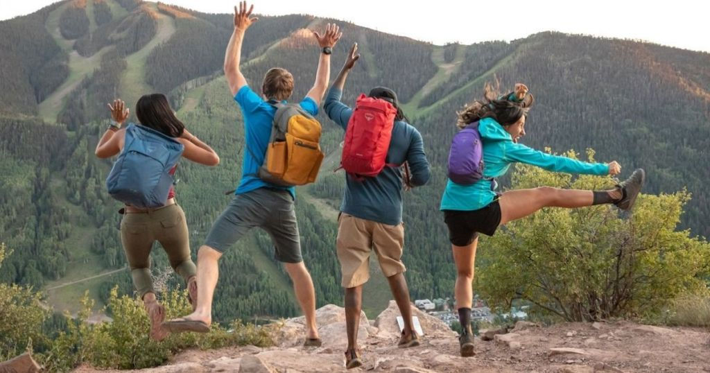 Group of people leaping in air wearing Osprey Bags