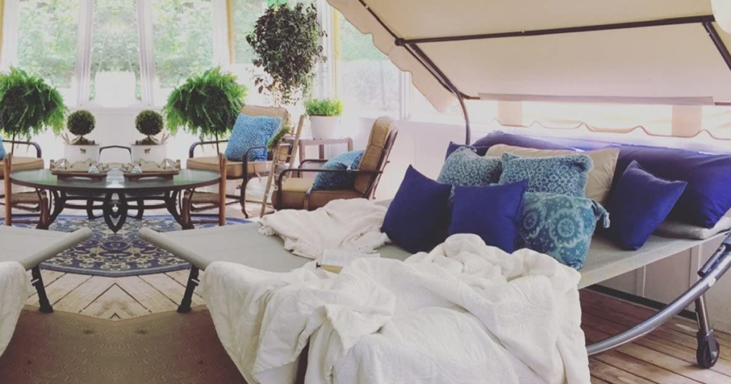 Double Hammock Bed with blue pillows and blanket on porch