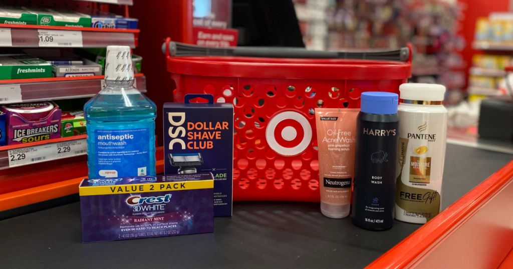 shampoo, mouthwash, razors and toothpaste in front of red basket
