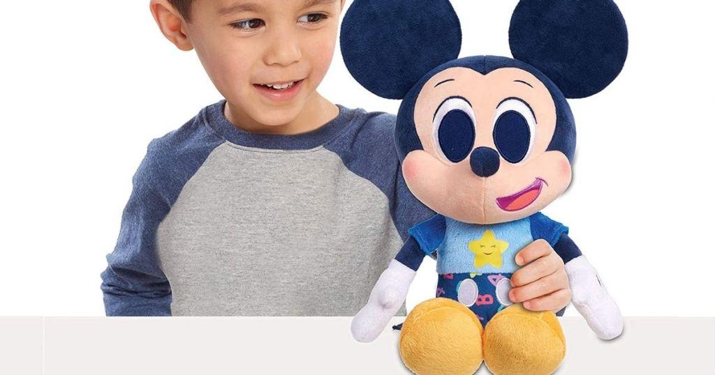 boy holding Mickey Mouse plush