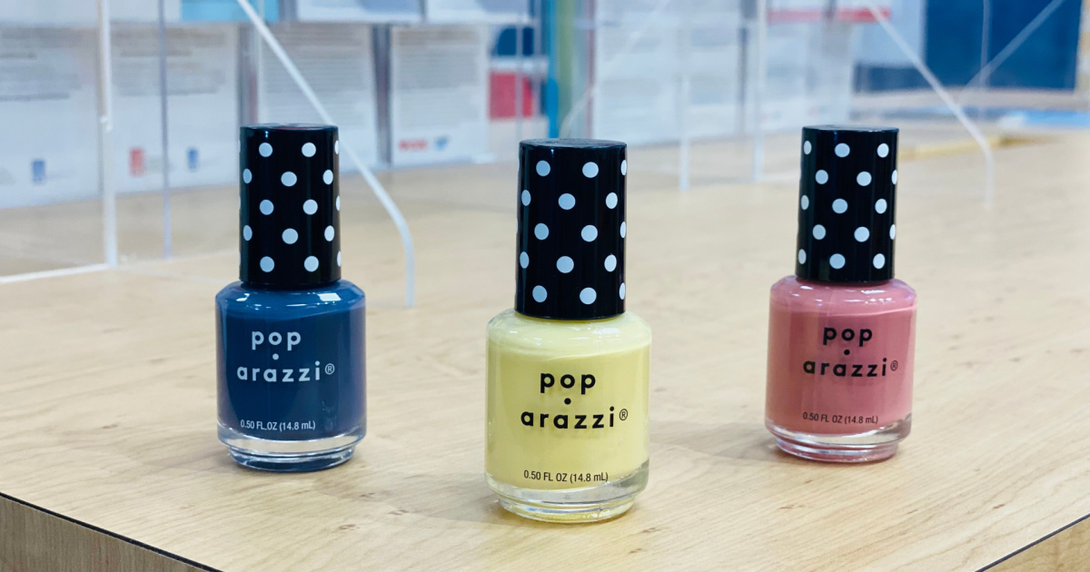 three bottles of nail polish on a table top - one blue, one yellow, one pink