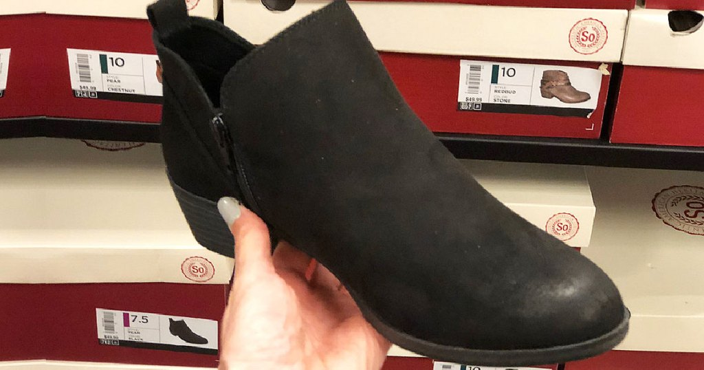 woman holding black bootie