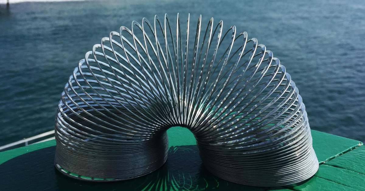 Slinky toy near water on green surface