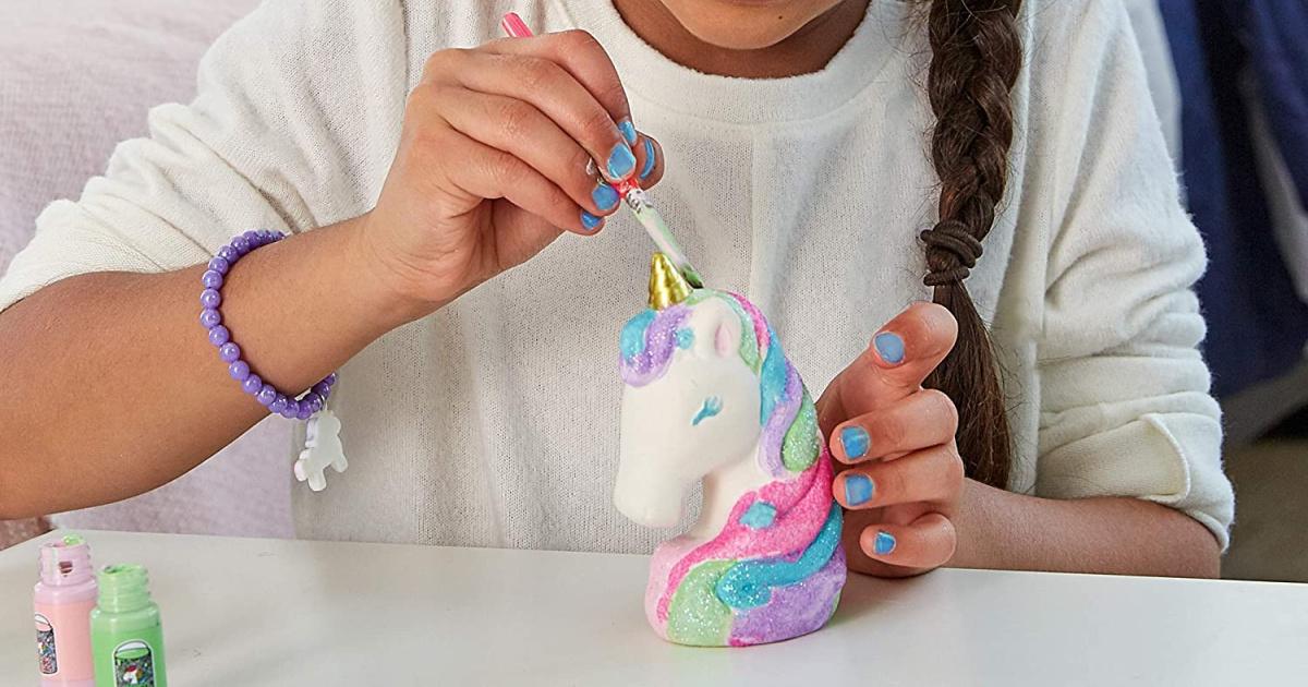 girl painting a unicorn figurine