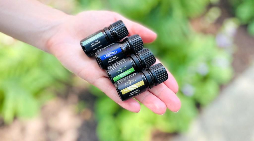 hand holding four mini bottles of anjou essential oils outside