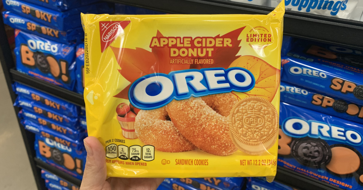 hand holding a package of apple cider donut oreos in front of a store display