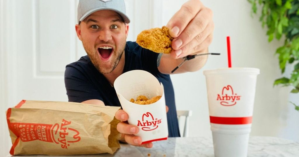man holding up Arby's chicken nugget