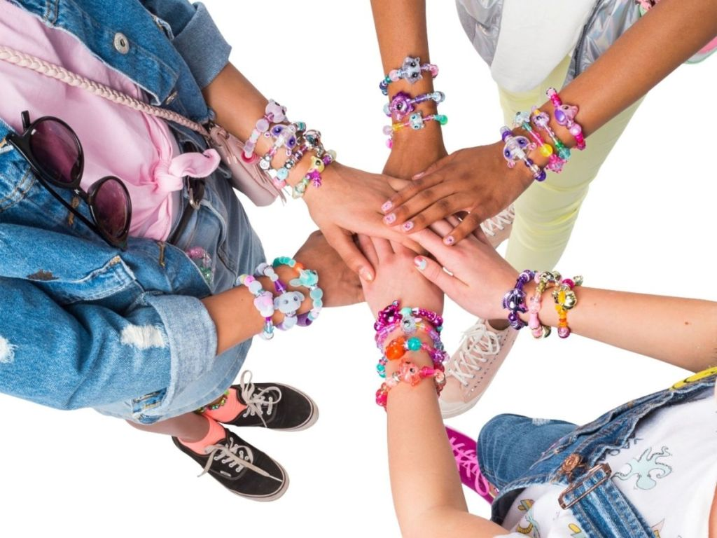girls putting hands over each others each wearing bracelets