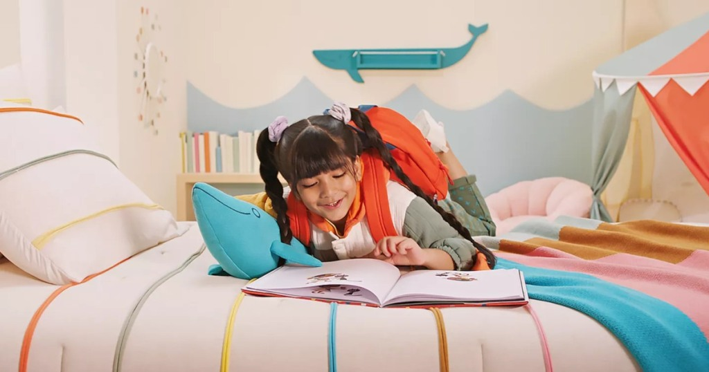 girl reading book on colorful bedding