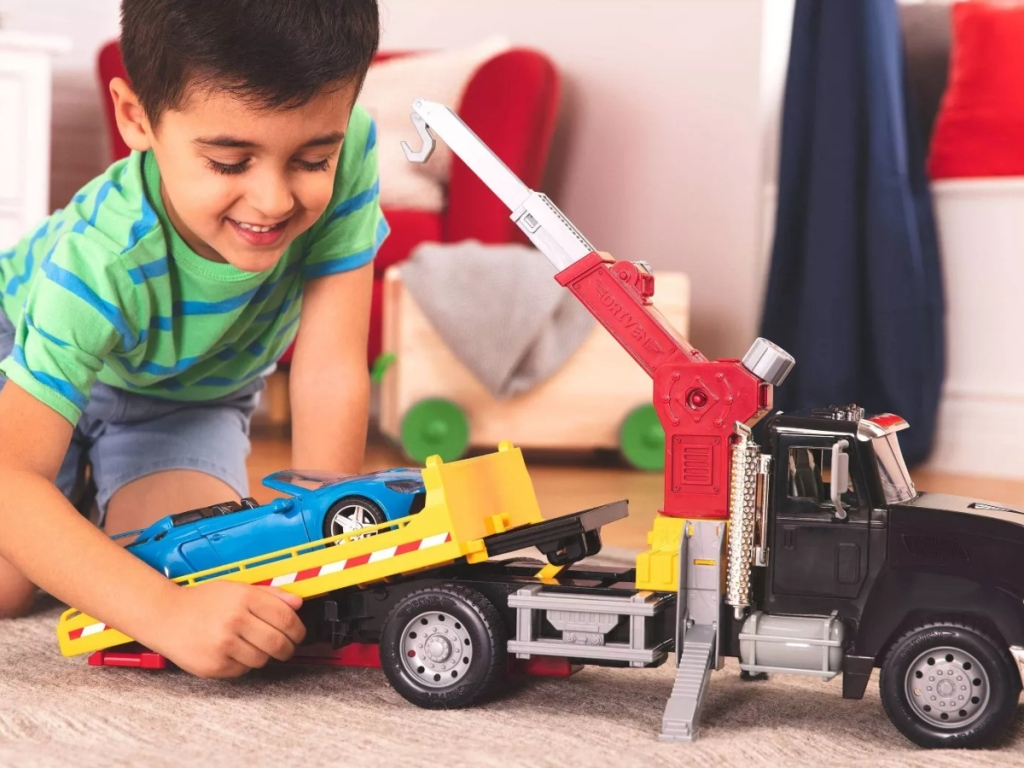 boy playing with toy tow truck
