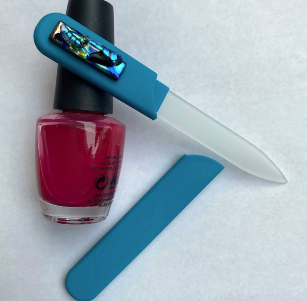 blue and clear glass nail file laying on white surface with bottle of nail polish