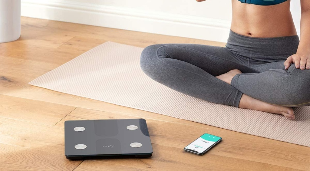 woman sitting near smart scale and phone with coordinating app