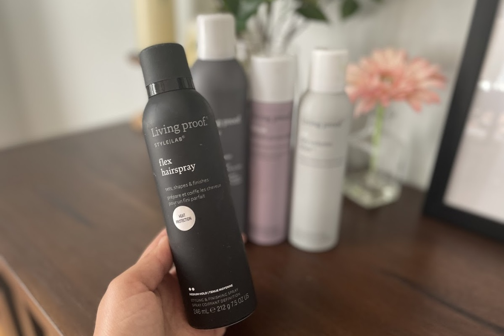Hand holding bottle of Living Proof Flex Hairspray
