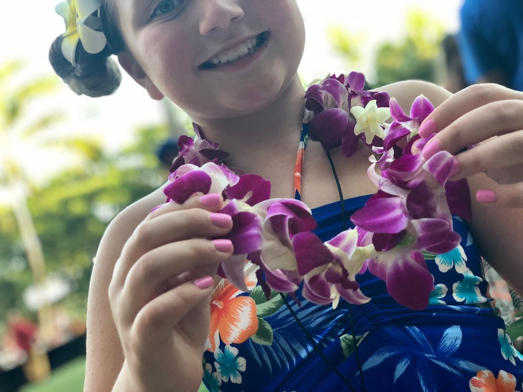 little girl wearing Hawaiian necklace and bathing suit