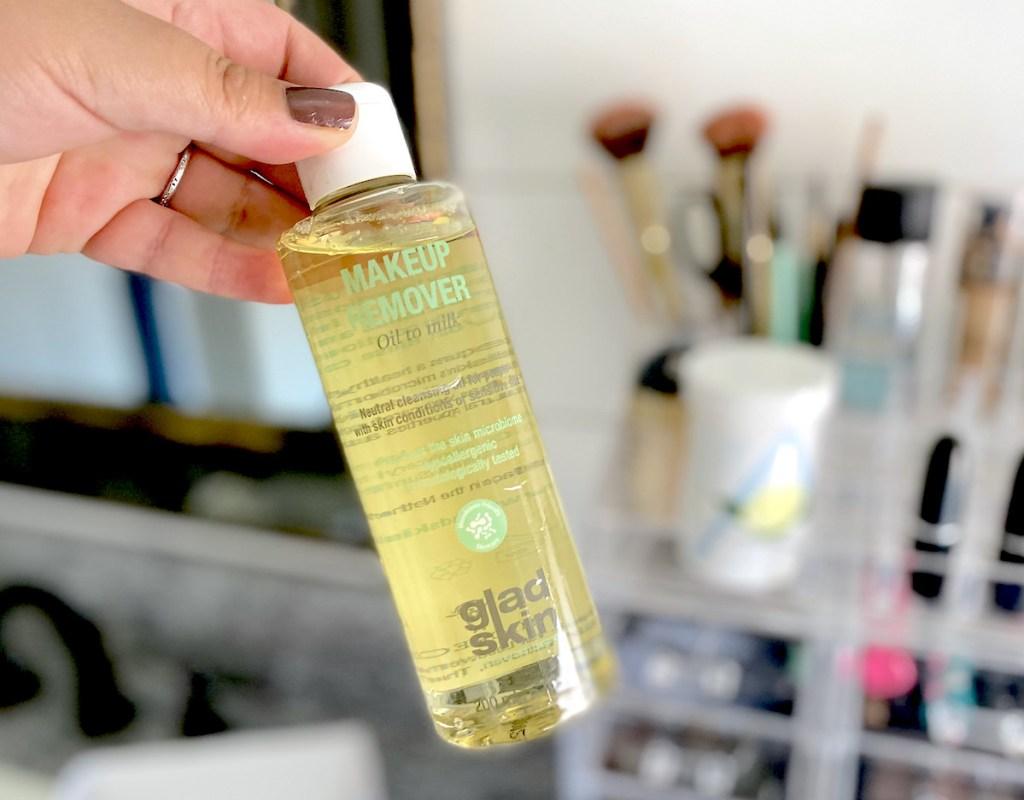 hand holding a bottle of gladskin makeup remover