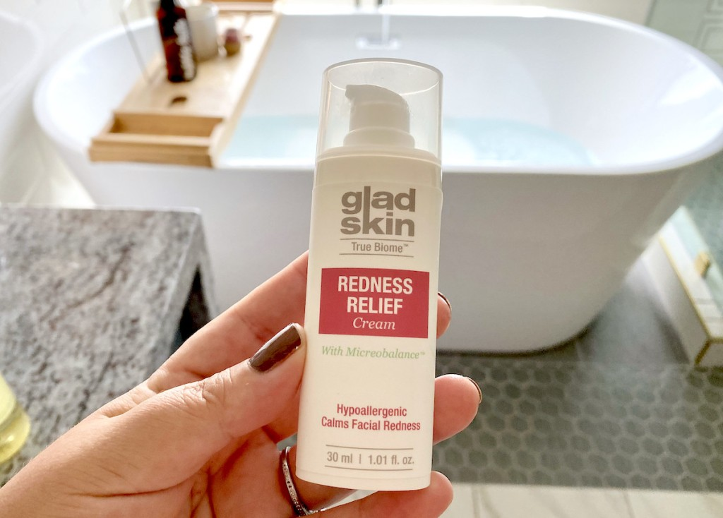 hand holding a bottle of gladskin skincare for redness relief cream in front of bathtub