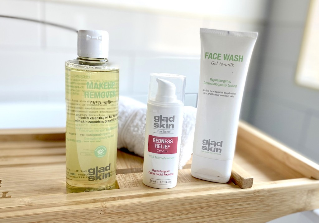 three gladskin skincare for redness beauty products sitting on bamboo tray in bathroom