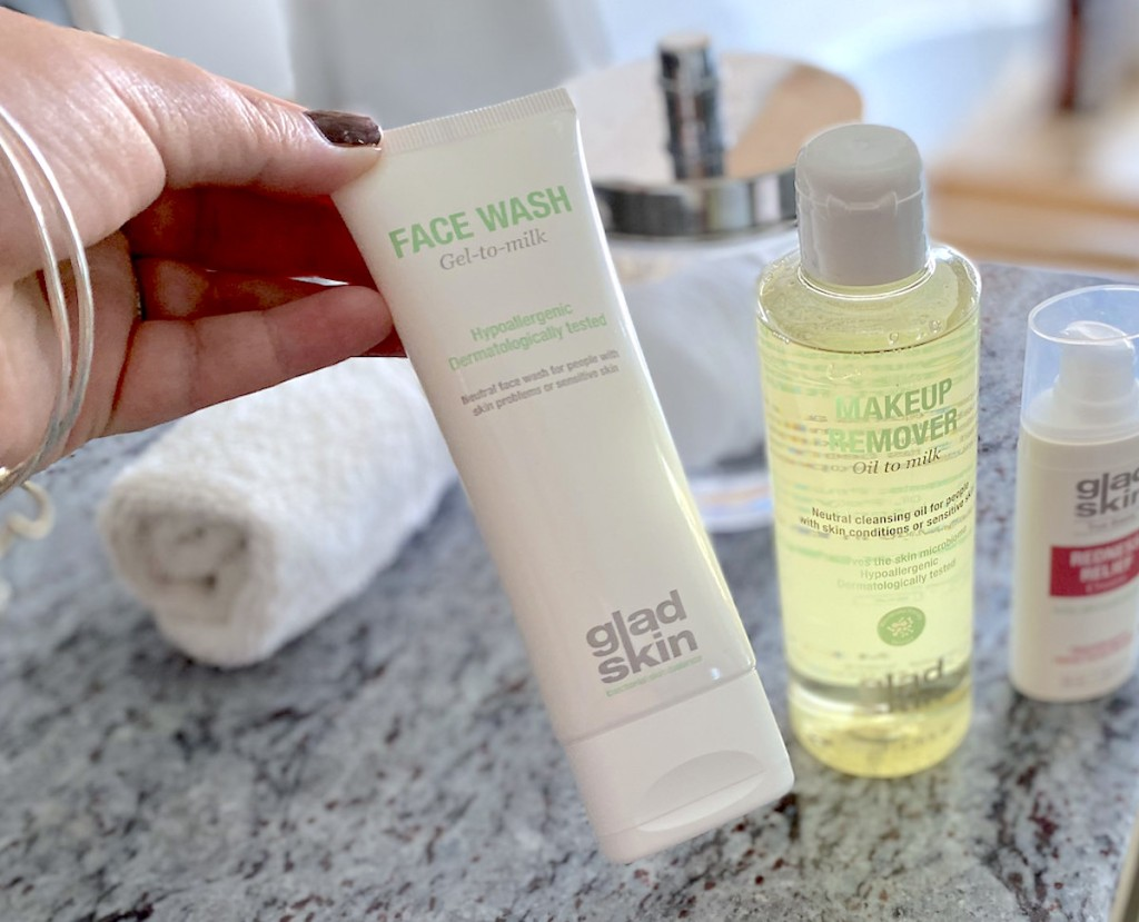 hand holding glad skin face wash and makeup remover on bathroom counter